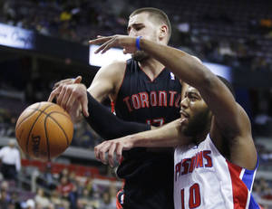 Photo -   Detroit Pistons center Greg Monroe (10) is fouled by Toronto Raptors center Jonas Valanciunas (17) while chasing a rebound in the first half of an NBA basketball game, Friday, Nov. 23, 2012, in Auburn Hills, Mich. (AP Photo/Duane Burleson)