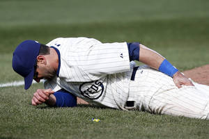 Photo - Chicago Cubs right fielder Justin Ruggiano holds his leg in the ninth inning of a baseball game against the Arizona Diamondbacks at Wrigley Field in Chicago on Wednesday, April 23, 2014. (AP Photo/Andrew A. Nelles)