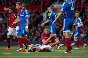 Photo - Manchester United's Phil Jones, bottom centre, sits injured on the pitch prior to being substituted, during his team's English Premier League soccer match against Hull City,  at Old Trafford Stadium, Manchester, England, Tuesday May 6, 2014. (AP Photo/Jon Super)