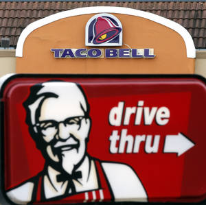 Photo - This Jan. 31, 2014 photo shows a Taco Bell facade behind a KFC drive-thru sign in Saugus, Mass. Fast-food conglomerate Yum! Brands, Inc., headquartered in Louisville, Ky., reports quarterly earnings on Tuesday, April 22, 2014. (AP Photo/Elise Amendola)