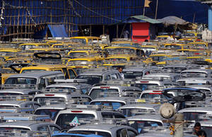 Photo -   Traditional black-and-yellow licensed cabs and private cabs stand at a parking lot at the airport in Mumbai, India.  AP Photo  <strong>Rajanish Kakade -  AP </strong>