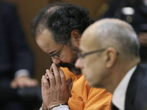 Photo - Ariel Castro looks down during court proceedings Friday, July 26, 2013, in Cleveland. Castro, who imprisoned three women in his home, subjecting them to a decade of rapes and beatings, pleaded guilty Friday to 937 counts in a deal to avoid the death penalty. Defense attorney Jaye Schlachet is on the right. (AP Photo/Tony Dejak)