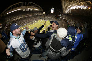 Photo - Seattle Seahawks fans celebrate after Seahawks' Michael Bennett recovered a New Orleans Saints fumble and scored a touchdown in the first half of an NFL football game, Monday, Dec. 2, 2013, in Seattle. (AP Photo/John Froschauer)