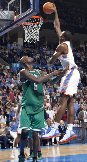 Photo - Oklahoma City Thunder power forward Serge Ibaka (9) dunks over Boston Celtics power forward Kevin Garnett (5) during the NBA basketball game between the Oklahoma City Thunder and the Boston Celtics at the Chesapeake Energy Arena on Wednesday, Feb. 22, 2012 in Oklahoma City, Okla.  Photo by Chris Landsberger, The Oklahoman