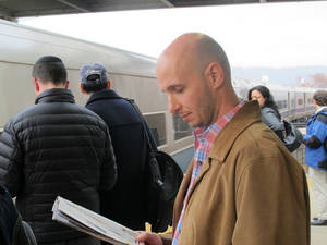 Photo - Matthew Adam, 37, prepares to board a Metro-North Railroad commuter train at the Spuyten Duyvil station in the Bronx borough of New York, on Wednesday, Dec. 4, 2014. The station reopened Wednesday, three days after a nearby derailment killed four people. (AP Photo/Jim Fitzgerald)