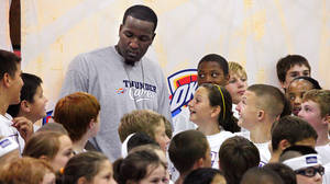 Photo - Oklahoma City Thunder NBA basketball player Kendrick Perkins surrounded by camp participants after posing for a group photograph at a Thunder Youth Camp at Mid-America Christian University, Monday,  June 6, 2011.  Photo by Jim Beckel, The Oklahoman ORG XMIT: KOD