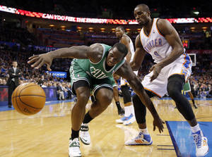 Photo - Boston Celtics forward Brandon Bass, left, reaches for the ball in front of Oklahoma City Thunder forward Serge Ibaka (9) in the second quarter of an NBA basketball game in Oklahoma City, Sunday, Jan. 5, 2014. (AP Photo/Sue Ogrocki)