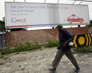 photo -   In this photo taken, Monday, Sept.17, 2012. An unidentified man walk past a Google advert in Lagos, Nigeria. With all its cutting-edge technology, Google Inc. has turned back to the text message in its efforts to break into Nigeria's booming economy. The search engine has started a service in Nigeria, as well as Ghana and Kenya, allowing mobile phone users to access emails through text messaging. That comes as the company's office in Lagos has begun working with small business owners in this nation of more than 160 million people. (AP Photo/Sunday Alamba)