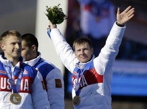 Photo - FILE - In this Sunday, Feb. 23, 2014 file photo, the team from Russia RUS-1, with Alexander Zubkov, right, Alexey Negodaylo, Dmitry Trunenkov, and Alexey Voevoda, wave to the crowd after they received the gold medal during the men's four-man bobsled competition final at the 2014 Winter Olympics, in Krasnaya Polyana, Russia. Olympic bobsled champion Alexander Zubkov was injured after unknown attackers smashed up the car he received for winning two gold medals at the Sochi Games. Zubkov was involved in a confrontation outside his Moscow home on Thursday, May 29, 2014, when attackers with bats smashed the lights and windshield of his Mercedes-Benz, one of the cars given by the Russian state to each of the country's gold medalists in Sochi. (AP Photo/Natacha Pisarenko, File)