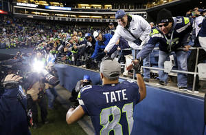 Photo - Seattle Seahawks' Golden Tate greets fans as he leaves the field after the team beat the St. Louis Rams in an NFL football game, Sunday, Dec. 29, 2013, in Seattle. The Seahawks won 27-9. (AP Photo/Elaine Thompson)