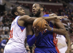 Photo - Detroit Pistons' Greg Monroe, right, is fouled by Philadelphia 76ers' Hollis Thompson (31) as he drives to the basket in the first half of an NBA basketball game on Friday, Jan. 10, 2014, in Philadelphia. (AP Photo/Laurence Kesterson)