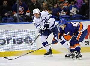 Photo - Tampa Bay Lightning B.J. Crombeen (19) shoots the puck past New York Islanders' Aaron Ness (55) in the first period of an NHL hockey game on Tuesday, Dec. 17, 2013, in Uniondale, N.Y. (AP Photo/Kathy Kmonicek)