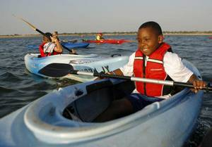 Photo - Justice Clark, 9 of Oklahoma City, takes a break from paddling.  Children and mentors of Big Brothers Big Sisters participated in kayaking at Lake Hefner in Oklahoma City, Thursday, July 28, 2011.  Photo by Garett Fisbeck, The Oklahoman ORG XMIT: KOD