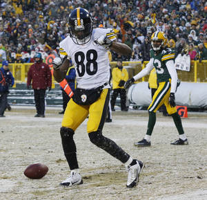 Photo - Pittsburgh Steelers' Emmanuel Sanders (88) celebrates his touchdown catch in front of Green Bay Packers' M.D. Jennings during the first half of an NFL football game Sunday, Dec. 22, 2013, in Green Bay, Wis. (AP Photo/Mike Roemer)