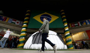 Photo - In this Tuesday, June 10, 2014 photo, a man walks near a shopping center where a large Brazil flag and half of a soccer ball decorate the entrance in Sao Paulo, Brazil. Soccer fans will focus on Brazil and the start of the World Cup on Thursday, but investors have been pumped up about that nation's stock market for months. (AP Photo/Julio Cortez)