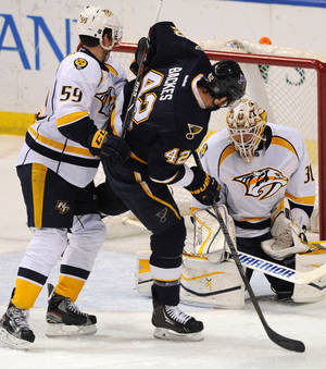 Photo - St. Louis Blues' David Backes (42) scores on Nashville Predators goalie Carter Hutton (31) as Predators' Roman Josi (59), of Switzerland, defends during the second period of an NHL hockey game Saturday, Feb. 1, 2014, in St. Louis. (AP Photo/Bill Boyce)