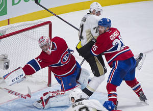 Photo - Montreal Canadiens goaltender Carey Price, left, loses his stick as Pittsburgh Penguins center Evgeni Malkin, center, moves in and Canadiens defenseman Josh Gorges defends during second-period NHL hockey game action in Montreal, Saturday, Nov. 23, 2013. (AP Photo/The Canadian Press, Graham Hughes)