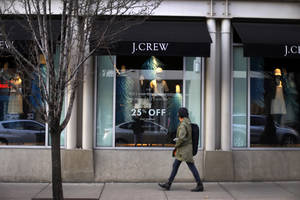 Photo - In this March 24, 2014 photo, a pedestrian passes a J.Crew store in the Shadyside shopping district of Pittsburgh. The Commerce Department reports on retail sales for March on Monday, April 14, 2014. (AP Photo/Gene J. Puskar)
