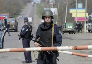 Photo - A Ukrainian soldier controls a road  outskirts of Izyum, Eastern Ukraine, Thursday, April 17, 2014. Ukraine is hoping to placate Russia and calm hostilities with its neighbor even as the U.S. prepares a new round of sanctions to punish Moscow for what it regards as fomenting unrest. (AP photo/Efrem Lukatsky)