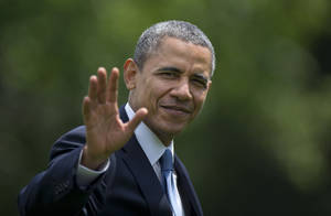 Photo - President Barack Obama waves as he walks from the Marine One helicopter to the Oval Office of the White House, in Washington,  Wednesday, May 28, 2014, as he returns from delivering the commencement address at the United States Military Academy at West Point, New York. (AP Photo/Carolyn Kaster)