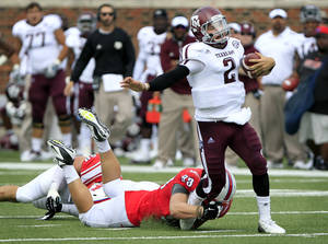 photo -   Texas A&M quarterback Johnny Manziel (2) struggles out of the grasp of SMU defensive tackle Aaron Davis (93) in route to the end zone for the team's second touchdown during an NCAA college football game on Saturday, Sept. 15, 2012, in Dallas. (AP Photo/John F. Rhodes)