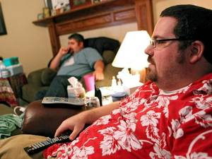 Photo - Alex Gates (right) and guests watch television during a Lost party at the home of Alex and Amber Gates in Moore, Okla., on Sunday, May 23, 2010. Photo by  John  Clanton