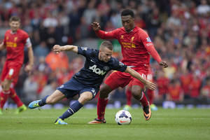Photo - Liverpool's Daniel Sturridge, right, fights for the ball against Manchester United's Tom Cleverley during their English Premier League soccer match at Anfield Stadium, Liverpool, England, Sunday Sept. 1, 2013. (AP Photo/Jon Super)