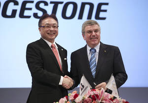 Photo - International Olympic Committee (IOC) President Thomas Bach, right, and Bridgestone Corp. CEO Masaaki Tsuya pose for photographers during a press conference in Tokyo, Friday, June 13, 2014. Japanese tire manufacturer Bridgestone signed an agreement on Friday to become a top-tier sponsor of the IOC in a 10-year deal that will cover the 2020 Tokyo Games. Bridgestone officials declined to reveal financial terms of the deal but the Asahi Shimbun newspaper reported that Bridgestone will pay $344 million to become a worldwide sponsor under the IOC's global commercial program, known as TOP. (AP Photo/Koji Sasahara)