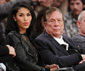 Photo - FILE - In this Dec. 19, 2010, file photo, Los Angeles Clippers owner Donald Sterling, third right, sits with V. Stiviano, left, as  they watch the Clippers play the Los Angeles Lakers during an NBA preseason basketball game in Los Angeles. NBA commissioner Adam Silver announced Tuesday, April 29, 2014, that he is banning the owner for life from the Clippers organization over racist comments in recording. (AP Photo/Danny Moloshok, File)