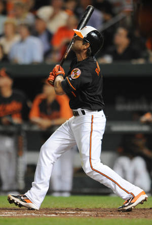 Photo - Baltimore Orioles' Brian Roberts watches his grand slam against the Oakland Athletics in the fourth inning of a baseball game on Friday, Aug. 23, 2013, in Baltimore. (AP Photo/Gail Burton)