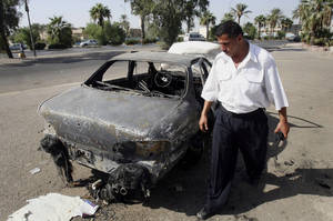 Photo - FILE - This Sept. 25, 2007 file photo shows an Iraqi traffic policeman inspecting a car destroyed by a Blackwater security detail in al-Nisoor Square in Baghdad, Iraq.  In a tale of death and destruction, a federal prosecutor has chronicled for a jury the alleged conduct of four Blackwater security guards accused of killing 14 Iraqis and wounding 18 others in downtown Baghdad nearly seven years ago. In opening statements Tuesday at the trial of the four guards, Assistant U.S. Attorney T. Patrick Martin said the victims were simply trying to get out of the way of gunfire from the Blackwater guards. (AP Photo/Khalid Mohammed, File)