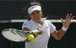 Photo - Li Na of China returns to Barbora Zahlavova Strycova of the Czech Republic during their women's singles match at the All England Lawn Tennis Championships in Wimbledon, London, Friday  June  27, 2014. (AP Photo/Pavel Golovkin)
