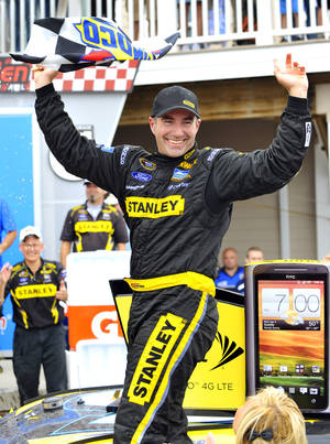 Photo -   Marcos Ambrose stands on his car in victory lane as he celebrates his win at the NASCAR Sprint Cup Series auto race at Watkins Glen International, Sunday, Aug. 12, 2012, in Watkins Glen, N.Y. (AP Photo/Autostock, Nigel Kinrade) MANDATORY CREDIT