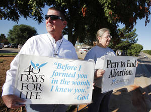 Photo - ANTI-ABORTION PRAYER VIGIL: Mark Daly and Deborah Krisch hold prayer vigil signs on NW 63rd in Warr Acres, October 1 , 2010. Photo by Steve Gooch, The Oklahoman ORG XMIT: KOD
