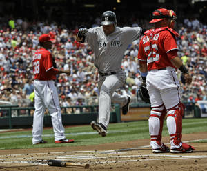 photo -   New York Yankees' Derek Jeter, center, scores on a sacrifice fly by Mark Teixeira as Washington Nationals catcher Jhonatan Solano (23) looks on during the first inning of a baseball game at Nationals Park, Sunday, June 17, 2012, in Washington. The Yankees won 4-1. (AP Photo/Alex Brandon)