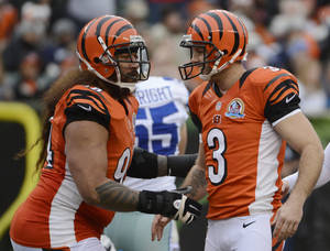photo - Cincinnati Bengals kicker Josh Brown (3) is congratulated by Domata Peko after Brown kicked a field goal against the Dallas Cowboys in the second half of an NFL football game, Sunday, Dec. 9, 2012, in Cincinnati. Brown kicked four field goals in the game won by Dallas 20-19. (AP Photo/Michael Keating)