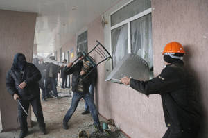 Photo - Pro-Russian men storm a police station in the eastern Ukrainian town of Horlivka on Monday, April 14, 2014.  Several government buildings have fallen to mobs of Moscow loyalists in recent days as unrest spreads across the east of the country. (AP Photo/Efrem Lukatsky)