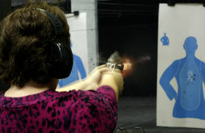 Photo - Peggy Osterholt, of Okarche, fires her handgun inside H&H Shooting Sports Complex in Oklahoma City. Photo by Bryan Terry, The Oklahoman