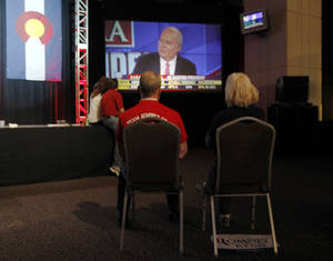 Photo -   A couple sits on chairs in a near-empty room to watch Fox News commentator Karl Rove on a big-screen television during a Republican Party election night gathering in the club level of Sports Authority Field at Mile High in Denver on Tuesday, Nov. 6, 2012. (AP Photo/David Zalubowski)