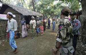 photo - In this photo taken on Nov. 10, 2012, Muslim refugees walk as Myanmar police officers stand guard at Sin Thet Maw relief camp in Pauktaw township, Rakhine state, western Myanmar.  Myanmars government has launched a major operation aimed at verifying the citizenship of Muslims in western Rakhine state, the coastal territory that has been torn apart by Buddhist-Muslim violence since June.  Questions over whether the region&#039;s Muslim Rohingya population qualify for citizenship are at the heart of a crisis that has killed nearly 200 people and displaced 110,000 more.    (AP Photo/Khin Maung Win)