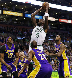 photo - Boston Celtics forward Kevin Garnett (5) shoots while surrounded by Los Angeles Lakers during the first half of an NBA basketball game in Boston, Thursday, Feb. 7, 2013. (AP Photo/Charles Krupa)