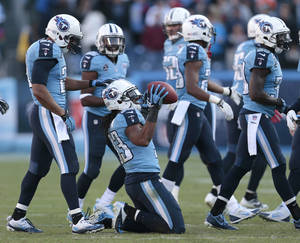 Photo - Tennessee Titans safety Michael Griffin (33) celebrates after intercepting a pass against the Houston Texans in the final minutes of the fourth quarter to seal a 16-10 win for the Titans in an NFL football game on Sunday, Dec. 29, 2013, in Nashville, Tenn. (AP Photo/Wade Payne)