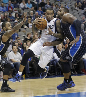 Photo - Dallas Mavericks shooting guard Monta Ellis, center, drives between Orlando forward Glen Davis and point guard Jameer Nelson during the second half of an NBA basketball game, Monday, Jan. 13, 2014, in Dallas. The Mavericks won 107-88.  (AP Photo/LM Otero)
