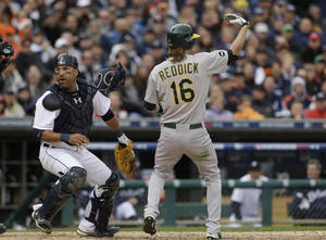 Photo -   Oakland Athletics' Josh Reddick (16) signals for teammate Yoenis Cespedes to run from third as Detroit Tigers catcher Gerald Laird chases a wild pitch during the eighth inning of Game 2 of the American League division baseball series, Sunday, Oct. 7, 2012, in Detroit. (AP Photo/Paul Sancya)