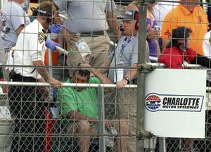 Photo - In this photo provided by Fernando Echeverria, security personnel assist a fan injured by a broken television camera cable during the NASCAR Sprint Cup series Coca-Cola 600 auto race at Charlotte Motor Speedway in Concord, N.C., Sunday, May 26, 2013. (AP Photo/Fernando Echeverria)