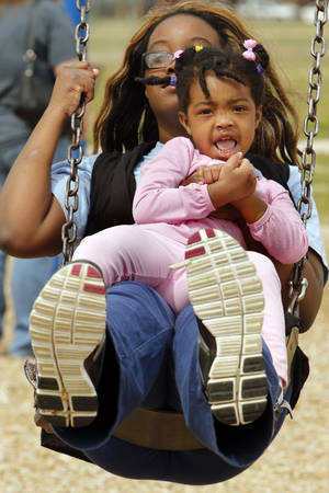 Photo - Jozette Masiah and daughter Talia, 3, swing Tuesday at Andrews Park in Norman.