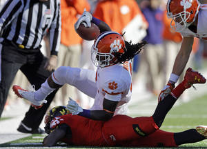 Photo - Clemson wide receiver Sammy Watkins, top, lands atop of Maryland defensive back Isaac Goins as he rushes the ball in the first half of an NCAA college football game in College Park, Md., Saturday, Oct. 26, 2013. (AP Photo/Patrick Semansky)