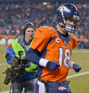 Photo - Denver Broncos quarterback Peyton Manning (18) runs off the field after the Broncos lost 27-20 to the San Diego Chargers in an NFL football game, Thursday, Dec. 12, 2013, in Denver. (AP Photo/Jack Dempsey)