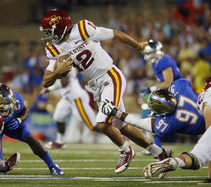 Photo - Iowa State's Sam Richardson (12)  is taken down Tulsa's Brentom Todd (97) during the first half of an NCAA college football game, Thursday, Sept. 26, 2013 in Tulsa, Okla. (AP Photo/Tulsa World, Tom Gilbert)  ONLINE OUT; TV OUT; TULSA OUT