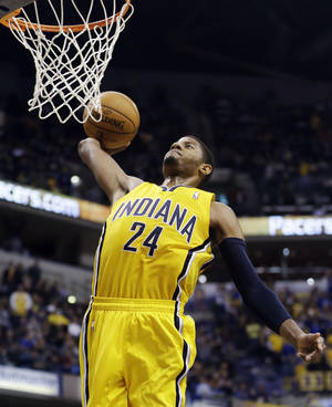 Photo - Indiana Pacers' Paul George goes in for a dunk during the second half of an NBA basketball game against the Memphis Grizzlies, Monday, Dec. 31, 2012, in Indianapolis. Indiana won 88-83. (AP Photo/Darron Cummings)